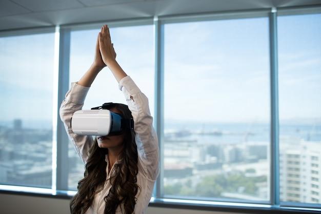 Geschäftsfrau, die yoga mit erhobenen armen unter verwendung der virtual-reality-brille praktiziert