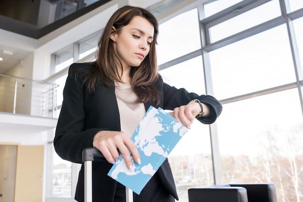 Geschäftsfrau, die zeit im flughafen prüft