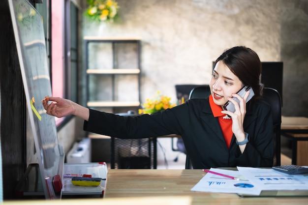 Geschäftsfrau, die zeitplan auf post-it überprüft und telefonisch mit kunden spricht.
