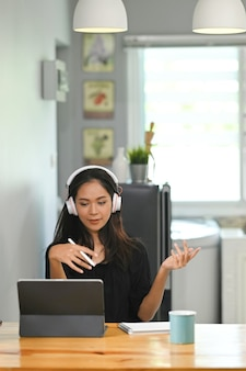 Geschäftsfrau, die zu hause am digitalen tablet arbeitet, während videoanrufkonferenz mit geschäftspartnergruppe.