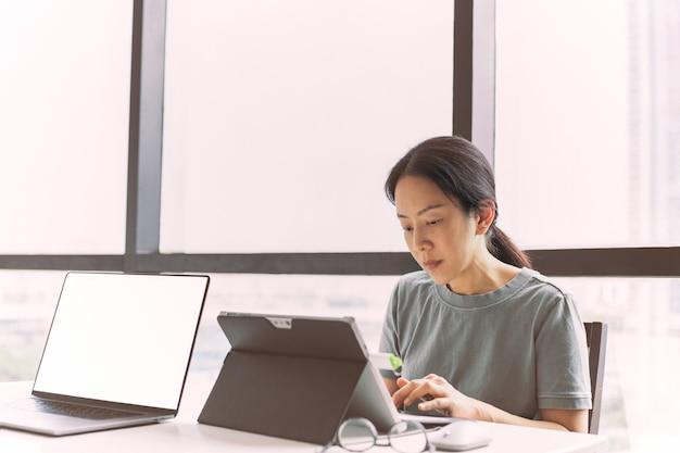 Geschäftsfrau, die zu hause an laptop-computer arbeitet