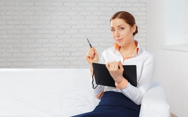 Geschäftsfrau, die zu hause büro für die planung und das schreiben auf ein notizbuch bearbeitet