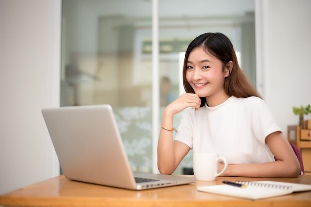 Geschäftsfrau, die zu hause mit laptop für das surfen des praktikanten arbeitet
