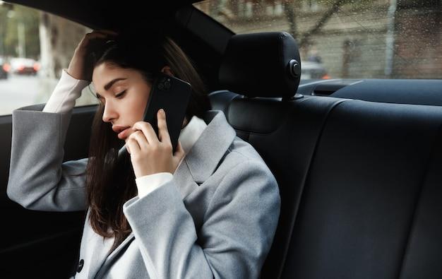 Geschäftsfrau, die zum büro in einem auto reist, das auf rücksitz sitzt und auf handy spricht
