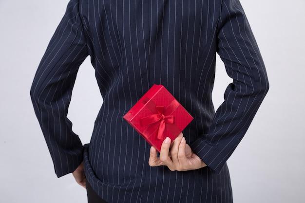 Geschäftsfrau, die zurück eine geschenkbox hinter ihr hält