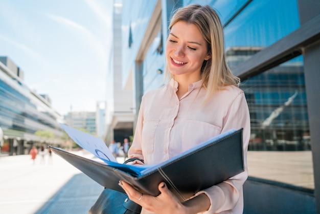 Geschäftsfrau, die zwischenablage hält und draußen steht