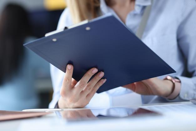 Geschäftsfrau, die zwischenablage mit dokumenten in ihren händen am arbeitsplatz hält
