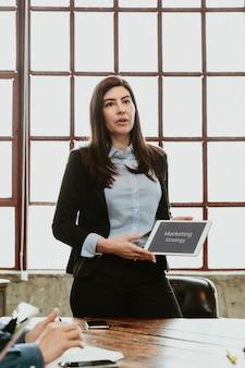 Geschäftsfrau diskutiert marketingstrategie mit einem tablet-mockup