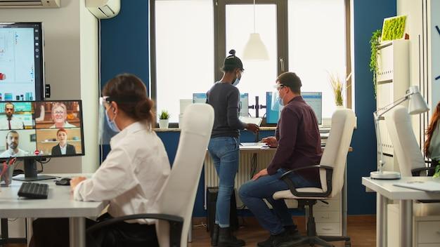 Geschäftsfrau diskutiert über webcam mit drahtlosem kopfhörer mit partnern aus der ferne, die eine schutzmaske tragen, die in einem modernen büro sitzt. mit videoanruf, kollegen, die die soziale distanz respektieren