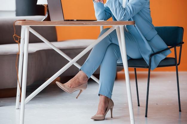 Geschäftsfrau drinnen im raum mit orangefarbener wand und holztisch.