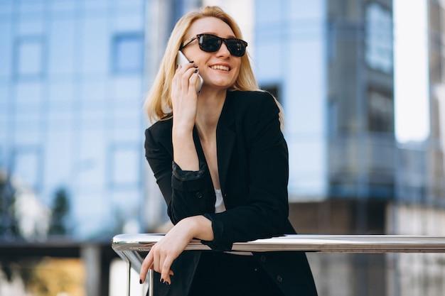 Geschäftsfrau durch den wolkenkratzer, der telefon verwendet