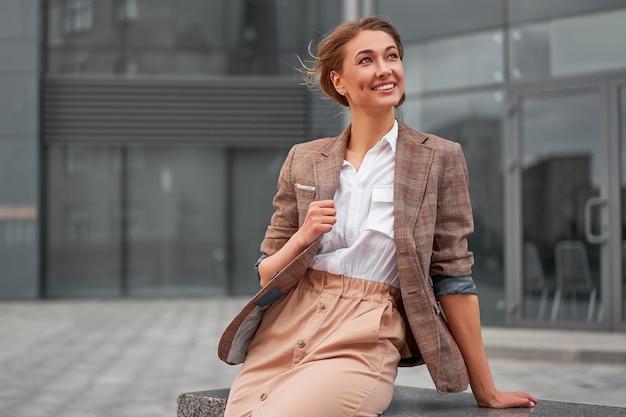 Geschäftsfrau erfolgreiche frau geschäftsperson stehende arme verschränkt außenunternehmensgebäude außen