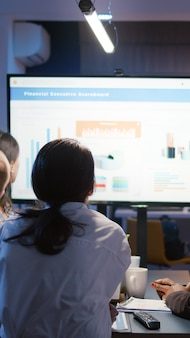 Geschäftsfrau erklärt finanzdiagramme mit präsentationsmonitor überarbeitung im büro