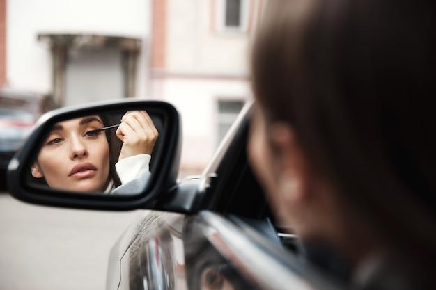Geschäftsfrau-fahrer, der rückspiegel betrachtet, während er im auto sitzt und wimperntusche anwendet