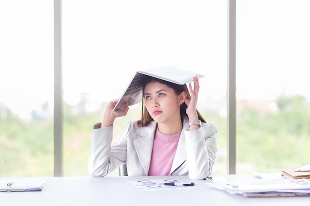 Geschäftsfrau gelangweilt von der arbeit mit vielem dokument und arbeit im laptop im büro