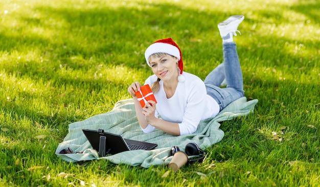 Geschäftsfrau geschäftlich nutzen computer aus dem büro im garten und frische luft. junge nachdenkliche frau mit laptop im park. freiberufler mit kaffee, der auf laptop auf grünem rasen in der natur arbeitet.