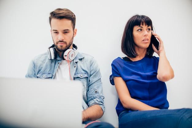 Geschäftsfrau gespräch am telefon neben ihrem partner