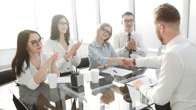 Geschäftsfrau gratuliert dem mitarbeiter mit der unterzeichnung eines neuen arbeitsvertrags. das konzept des karrierewachstums