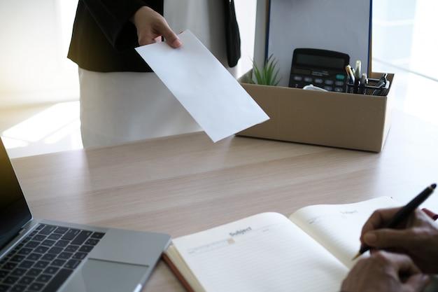 Geschäftsfrau haben boxen für den persönlichen gebrauch und senden kündigungsschreiben an führungskräfte