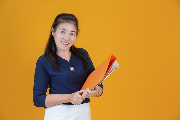 Geschäftsfrau hält datei in orange