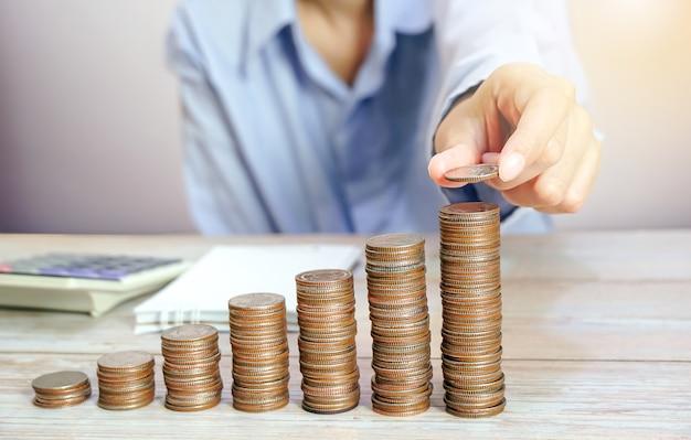 Geschäftsfrau hält die münze an die spitze des höchsten münzstapels