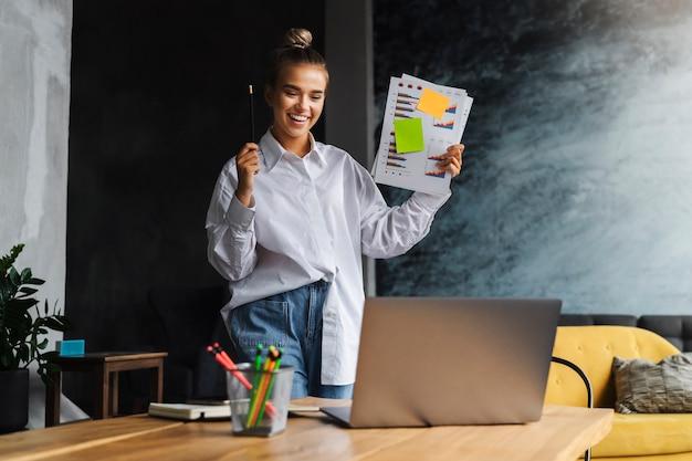 Geschäftsfrau hält dokumente, kommuniziert über webkamera.