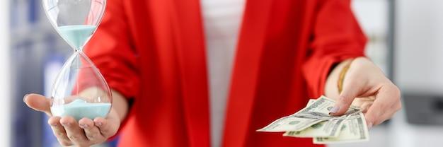 Geschäftsfrau hält eine sanduhr und hundert dollarnoten in den händen. zeitmanagement im geschäftskonzept
