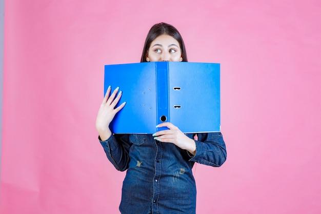 Geschäftsfrau hält einen offenen projektordner und versteckt ihr gesicht dahinter