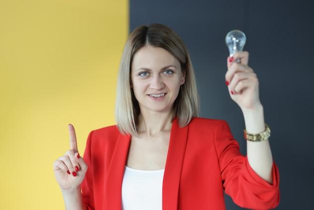 Geschäftsfrau hält glühbirne und dreht sich auf den kopf. entwicklungskonzept für kleine und mittlere unternehmen
