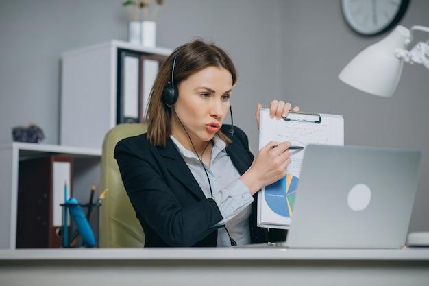 Geschäftsfrau hält papier finanzbericht gespräch bei webcam videoanruf im büro