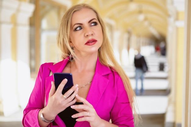 Geschäftsfrau hält smartphone in händen, während sie in gewölbter handelsgalerie steht.