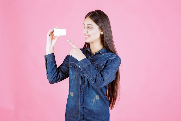 Geschäftsfrau hält und zeigt auf ihre visitenkarte