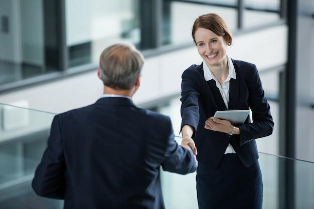 Geschäftsfrau händeschütteln mit ihrem kollegen