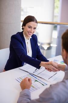 Geschäftsfrau händeschütteln mit kollege am schreibtisch