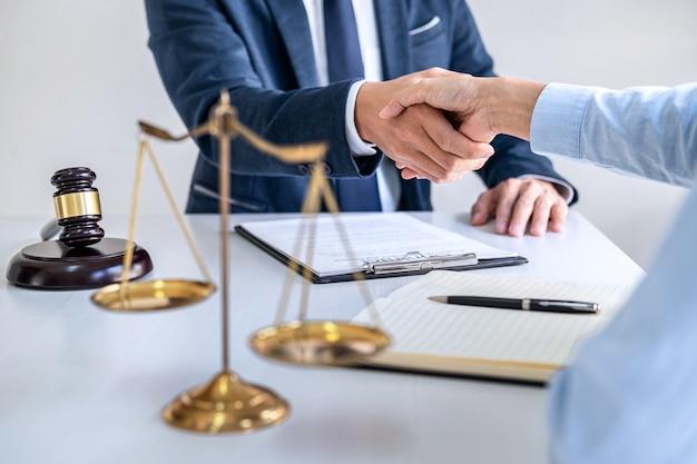 Geschäftsfrau händeschütteln mit männlichem anwalt nach besprechung vieler verträge im gerichtssaal
