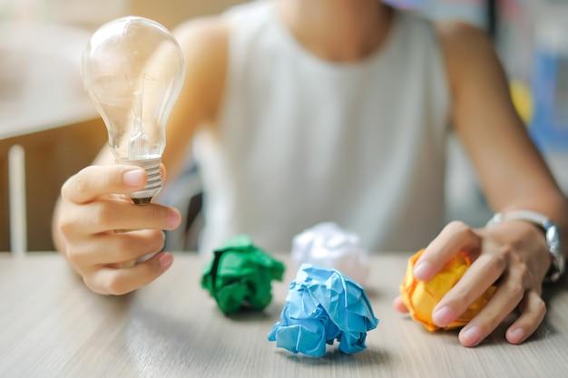 Geschäftsfrau hand, die glühlampe oder lampe mit buntem zerknittertem papier hält