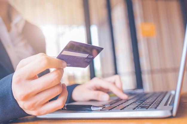 Geschäftsfrau hand hält eine blaue kreditkarte.