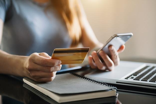 Geschäftsfrau hand mit smartphone, tablet-zahlungen und kreditkarten-online-shopping, omni-channel, digitaler tablet-docking-tastaturcomputer im büro im sonnenlicht