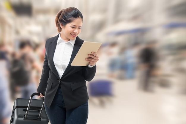 Geschäftsfrau hand mit tablet beim tragen von gepäck
