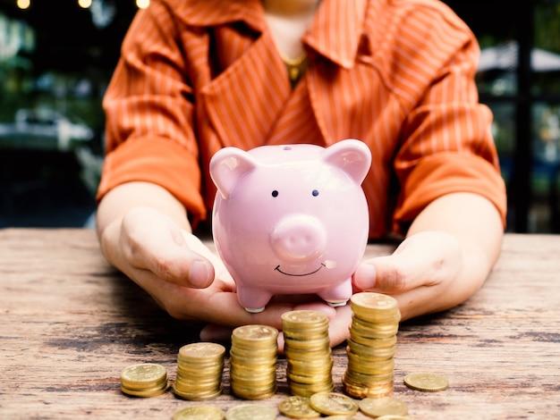 Geschäftsfrau hand tragen rosa sparschwein mit goldmünzen haufen wachstumsdiagramm, geld sparen für zukünftige investitionspläne und pensionsfondskonzept.