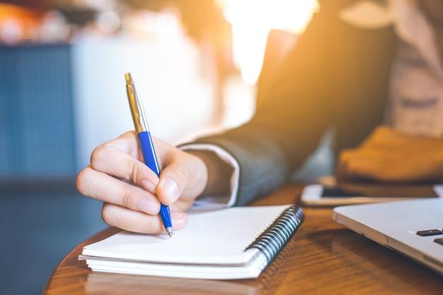 Geschäftsfrau-handschrift auf notizblock mit einem stift im büro.