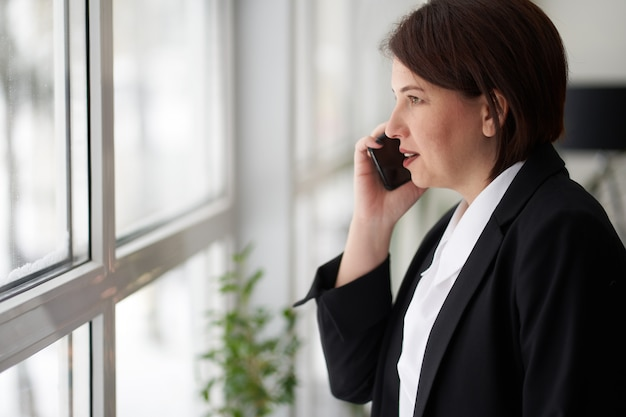 Geschäftsfrau hat telefongespräch nahe bürofenster. manager, arbeitgeber.