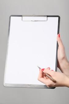 Geschäftsfrau holding a clipboard and writing