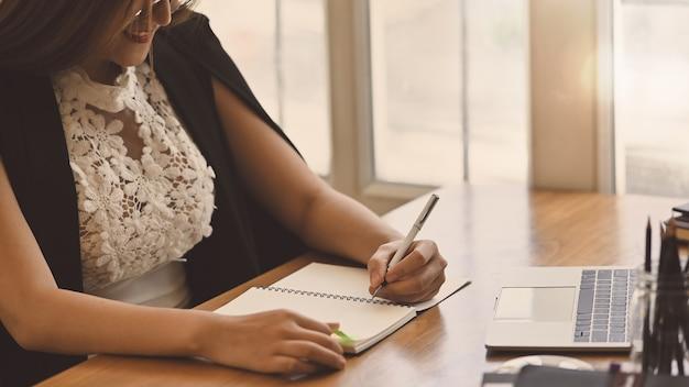 Geschäftsfrau ihr schreiben auf notizbuchpapier