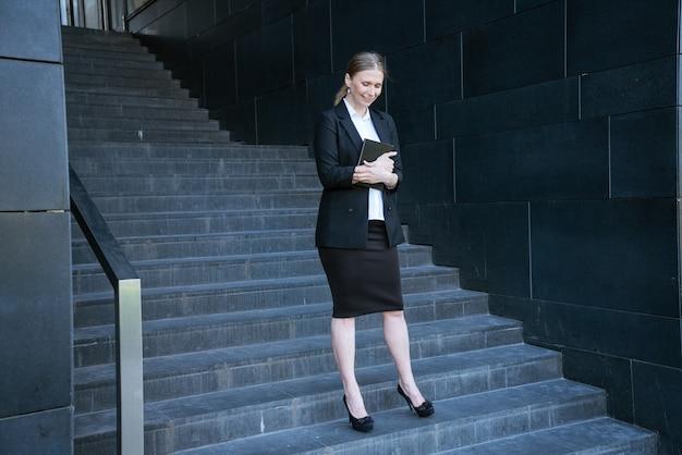 Geschäftsfrau im anzug mit tagebuch steht auf den stufen