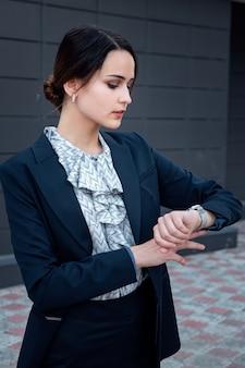 Geschäftsfrau im anzug schaut auf die uhr im freien.