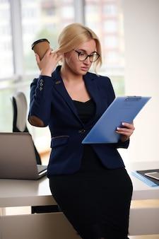 Geschäftsfrau im anzug sitzt am schreibtisch mit laptop.
