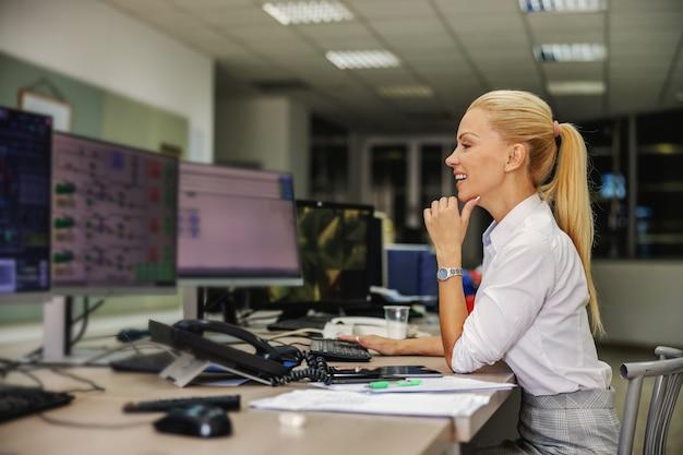 Geschäftsfrau im anzug sitzt im kontrollraum im heizwerk und benutzt computer.