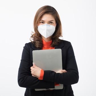 Geschäftsfrau im anzug tragen einen computer und verwenden eine maske, um vor coronavirus zu schützen