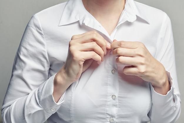 Geschäftsfrau im aufknöpfenden hemd der weißen bluse